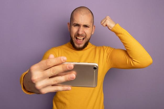 Возбужденный молодой красивый парень держит и смотрит на телефон, показывая жест да, изолированный на фиолетовом