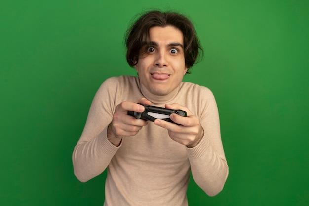 Возбужденный молодой красивый парень, держащий джойстик игрового контроллера, изолированный на зеленой стене