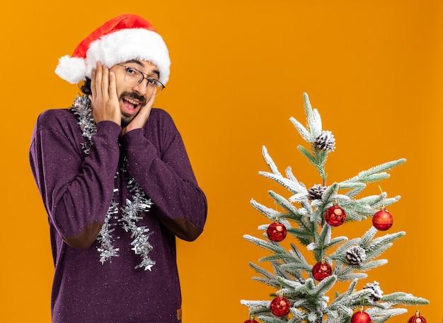 オレンジ色の背景で隔離の頬に手を置いて首に花輪とクリスマスの帽子をかぶってクリスマスツリーの近くに立っている興奮した若いハンサムな男