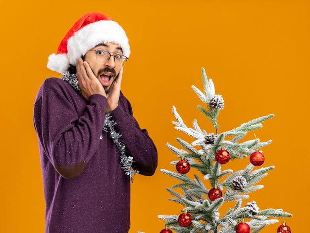 오렌지 벽에 고립 된 뺨에 손을 댔을 목에 갈 랜드와 함께 크리스마스 모자를 쓰고 크리스마스 트리 근처에 서있는 흥분된 젊은 잘 생긴 남자