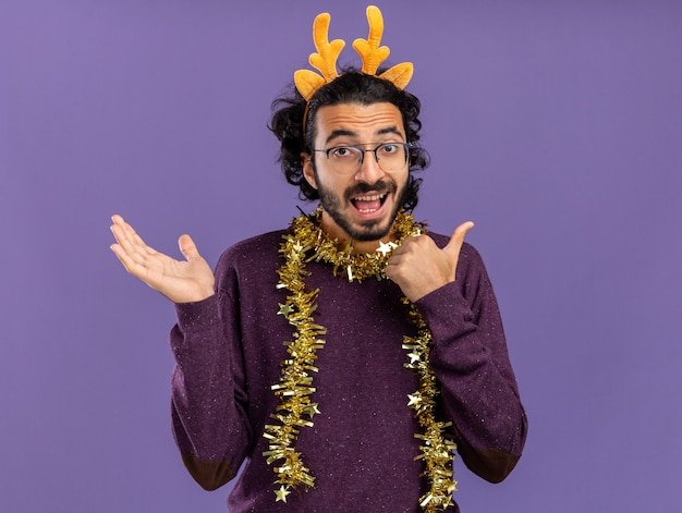 Excited young handsome guy wearing christmas hair hoop with garland on neck spreading hand and points at side isolated on blue background