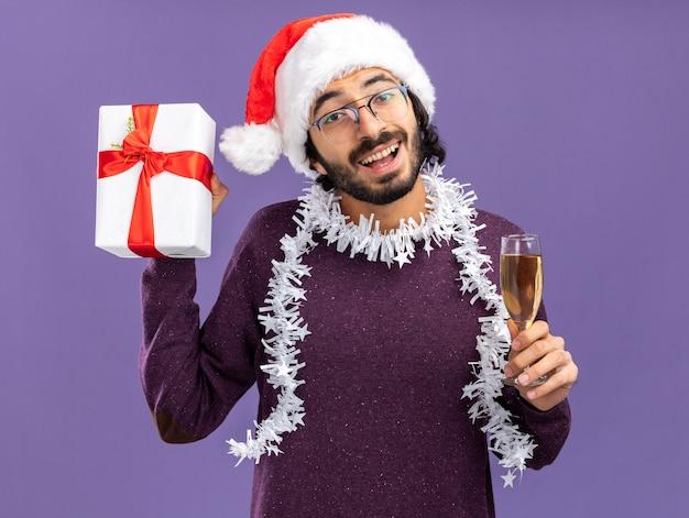 Eccitato giovane bel ragazzo che indossa il cappello di natale con la ghirlanda sul collo tenendo la confezione regalo con un bicchiere di champagne isolato su sfondo blu
