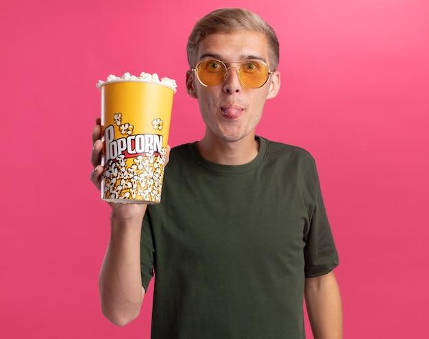 Eccitato giovane bel ragazzo che indossa la camicia verde e bicchieri tenendo il secchio di popcorn che mostra la lingua isolata sulla parete rosa