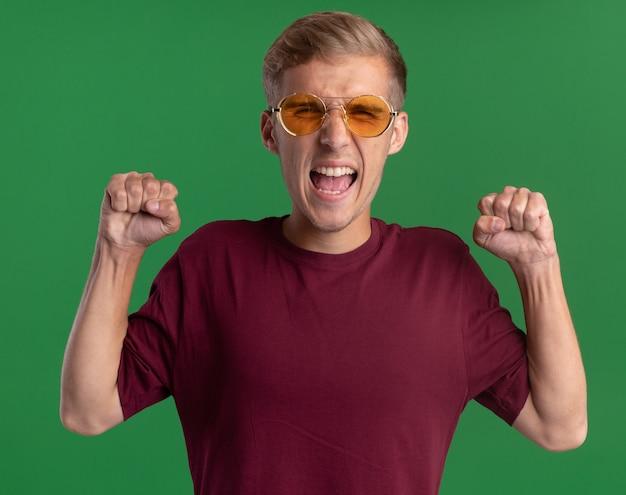 緑の壁に分離されたはいジェスチャーを示す赤いシャツと眼鏡を身に着けている興奮した若いハンサムな男