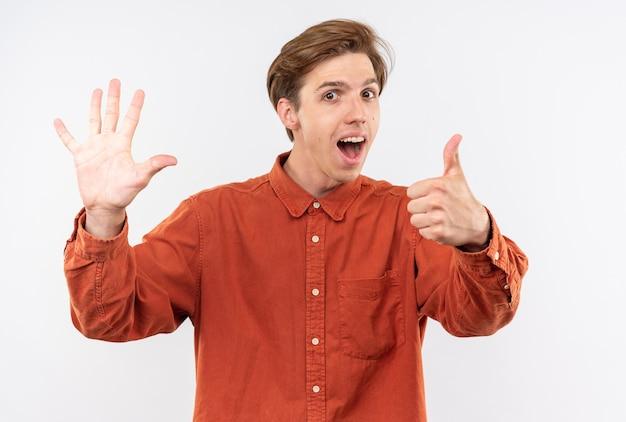 異なるジェスチャーを示す赤いシャツを着て興奮した若いハンサムな男