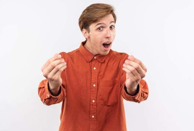 白い壁に分離された先端ジェスチャーを示す赤いシャツを着て興奮した若いハンサムな男