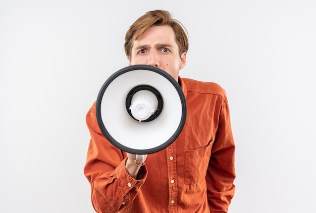Взволнованный молодой красивый парень в красной рубашке говорит по громкоговорителю, изолированному на белой стене