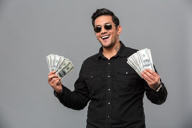 Excited young handsome man holding money.