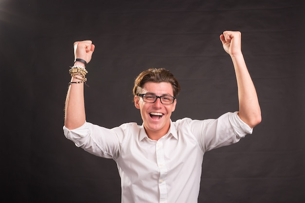 Excited young handsome man with fists up isolated over black wall