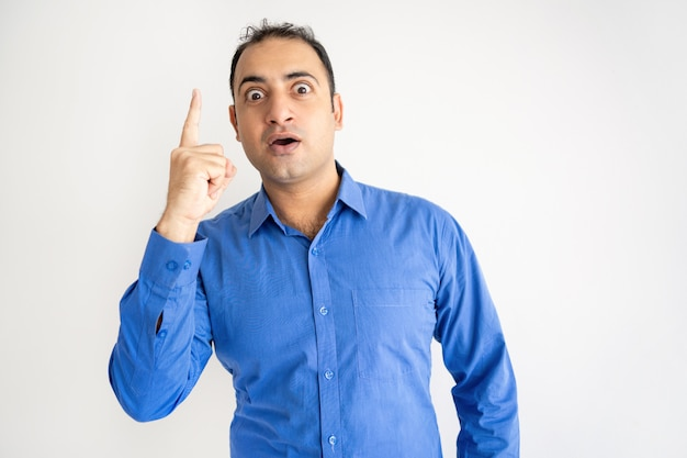 Excited young indian guy raising finger and looking at camera