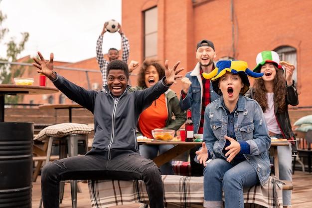 Взволнованные молодые межкультурные друзья с пивом и закусками болеют за свою команду во время просмотра трансляции футбольного матча