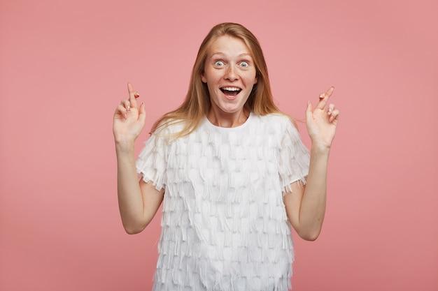ピンクの背景の上にポーズをとっている間、上げられた指を交差させたまま、広い目と口を開いてカメラを見てカジュアルな髪型の興奮した若い楽しいかわいい赤毛の女性