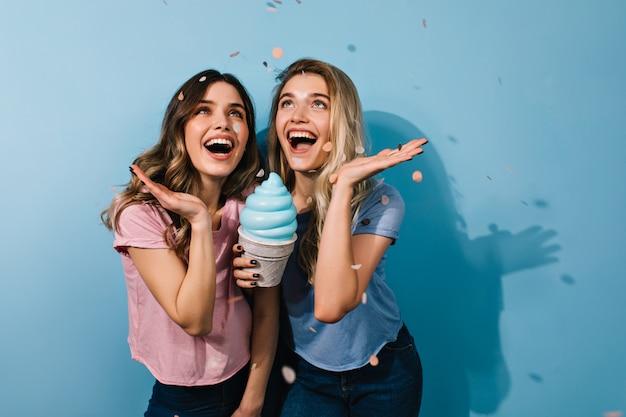 Giovani donne emozionanti che guardano in su sotto i coriandoli