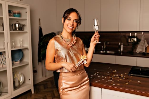 Eccitata giovane donna che indossa un vestito elegante che tiene un bicchiere di champagne e si prepara per la festa