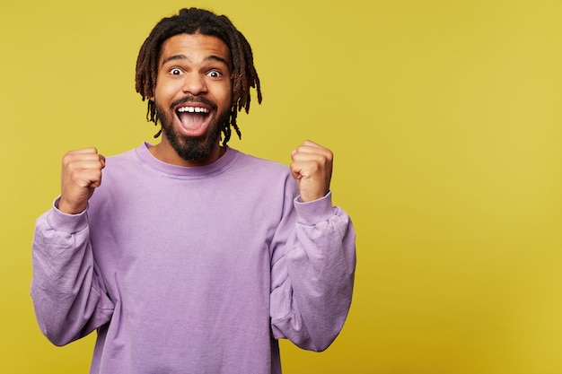 Excited young lovely dark skinned brunette man with dreadlocks looking surprisedly at camera with opened mouth and keeping his hands raised, isolated over yellow background