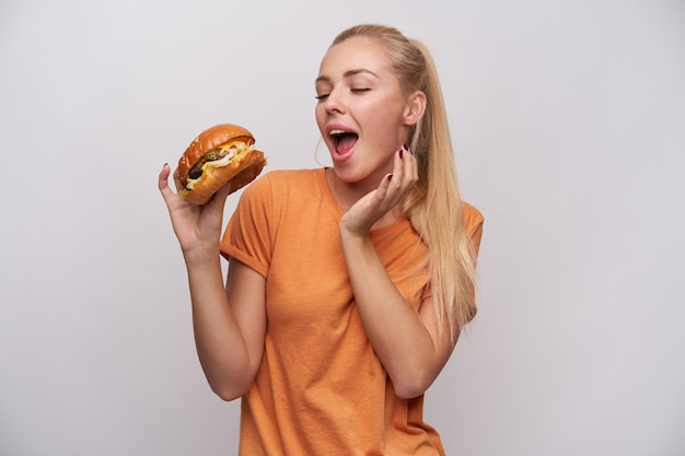 Excited young lovely long haired blonde lady in orange t-shirt foretasting delicious dinner while having hamburger in raised hand, smiling pleasantly while posing over white background