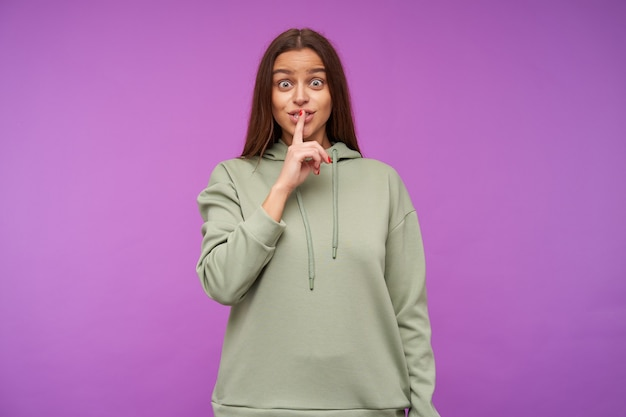 Excited young lovely long haired brunette lady raising hand with hush gesture to her mouth while looking positively at front, isolated over purple wall