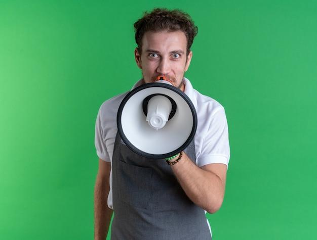 유니폼을 입고 흥분된 젊은 남성 이발사는 녹색 벽에 고립 된 스피커에 말한다