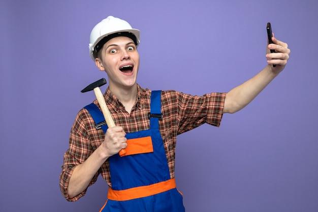 망치를 들고 제복을 입은 흥분된 젊은 남성 건축업자는 셀카를 찍습니다.