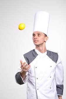 흰색 벽 배경 스튜디오 초상화에 고립 된 포즈 흰색 유니폼 셔츠에 젊은 남성 요리사 요리사 또는 베이커 남자를 흥분. 요리 음식 개념. 복사 공간을 모의합니다. 레몬을 손에 들고.