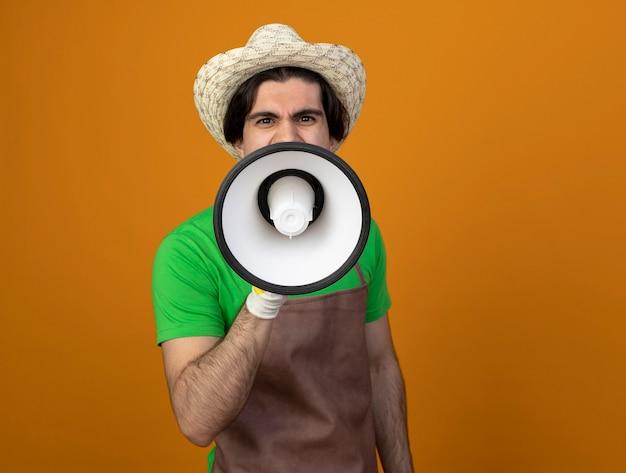 Excited young male gardener in uniform wearing gardening hat with gloves speaks on loudspeaker
