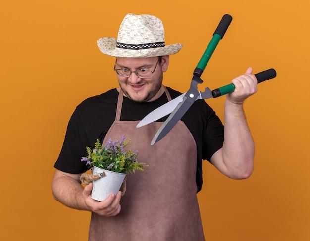 オレンジ色の壁に分離された植木鉢に花とバリカンを保持している園芸帽子と手袋を身に着けている興奮した若い男性の庭師