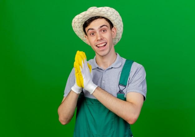 ガーデニングの帽子と手袋を身に着けている興奮した若い男性の庭師は、コピースペースで緑の背景に分離された手を一緒に保持します。