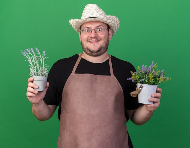Eccitato giovane giardiniere maschio che indossa il cappello di giardinaggio che tiene i fiori in vasi da fiori isolati sulla parete verde