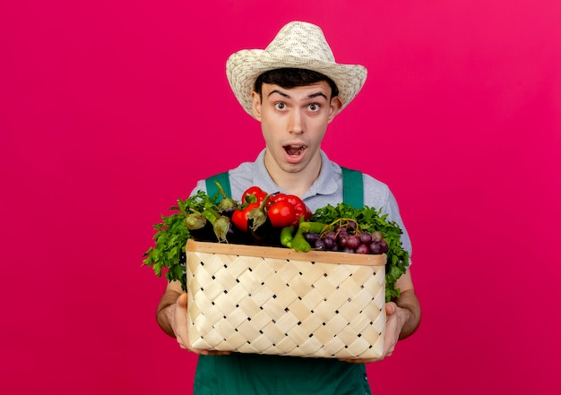 Excited young male gardener wearing gardening hat holds vegetable basket