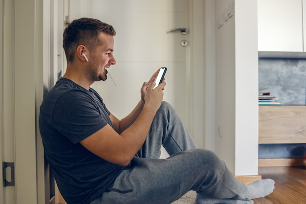 An excited young male person sits on the floor and uses a phone with a touch screen and holds the card in his mouth