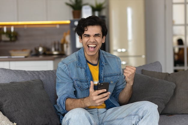 Excited young male with smartphone sit on couch at home reading unexpected good news on cellphone. happy man stunned surprised by online lottery win