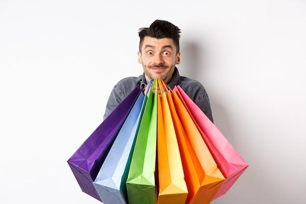 Возбужденный молодой человек несет красочные хозяйственные сумки и улыбается счастливым покупателем, покупающим на распродаже, стоя на белом фоне.