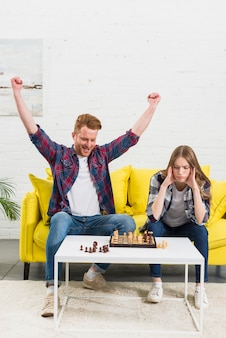 Excited young man celebrating his success after playing the chess game with girlfriend