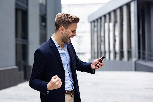 승리를 축하하는 흥분된 젊은 남자. 큰 성공, 큰 성취, 긍정적인 감정. 좋은 소식을 받고 스마트폰으로 잘생긴 사업가입니다.