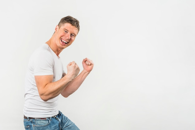 Excited young man clenching her fist against white background