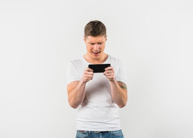 흰색 배경 핸드폰에 비디오 게임을 즐기는 흥분된 젊은 남자