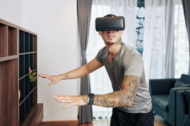 집에서 가상 현실 안경으로 비디오 게임을 즐기는 흥분된 청년