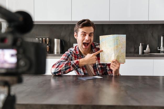 彼のビデオブログエピソードを撮影する興奮した若い男