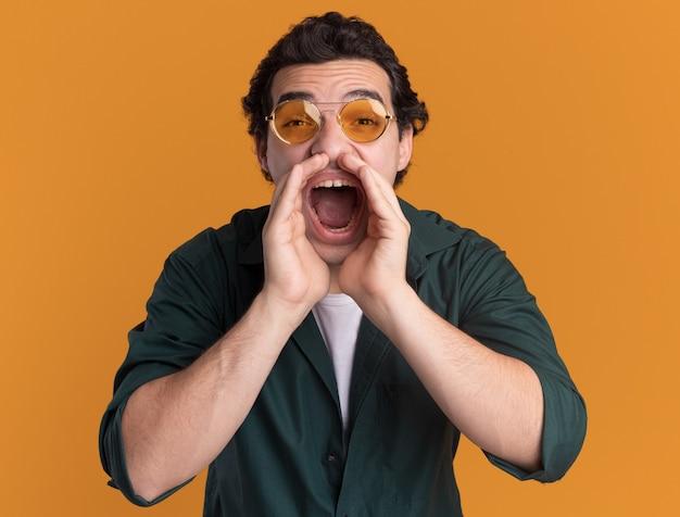 Eccitato giovane uomo in camicia verde con gli occhiali che grida con le mani vicino alla bocca in piedi sopra la parete arancione