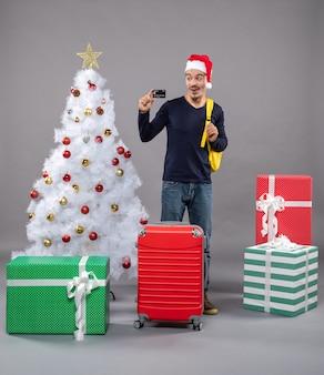 회색에 크리스마스 트리 근처 카드 서를 들고 흥분된 젊은 남자