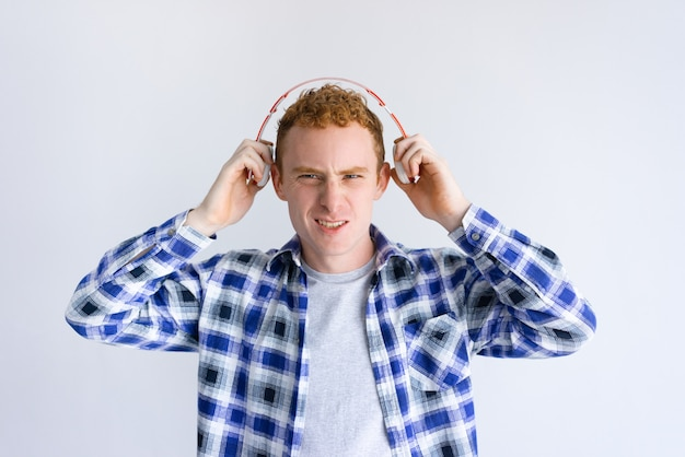 Excited young man holding headphones near ears