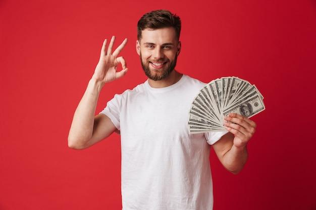 Взволнованный молодой человек, держащий деньги, делает хорошо жест.