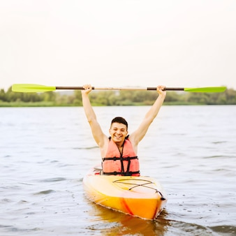 Excited young man holding oar in his hand kayaking on like