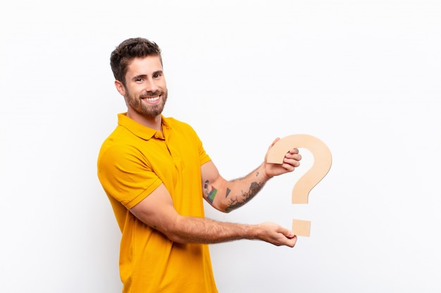 Excited young man holding the question mark symbol to form a word or a sentence