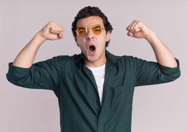 흰 벽 위에 서있는 승리를 축하하는 승자처럼 주먹을 올리는 정면을보고 안경을 쓰고 녹색 셔츠에 흥분된 젊은 남자