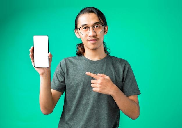 스마트폰을 제시하고 손가락으로 가리키는 회색 티셔츠를 입은 흥분된 청년