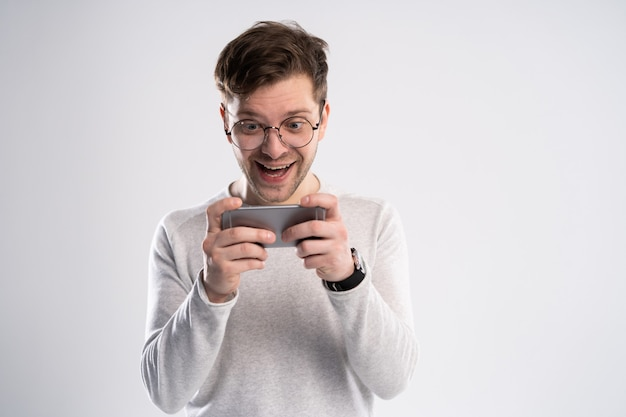 Взволнованный молодой человек в белой футболке играет в игры на мобильном телефоне, изолированном на белом фоне