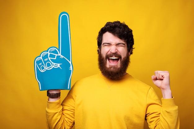 Excited молодой человек носит перчатку вентилятора пены пока делающ жест победителя.