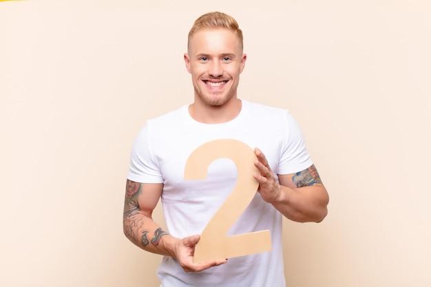 Возбужденный молодой человек радостно держит номер 2
