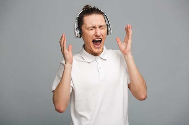 Excited young man listening music in headphones.